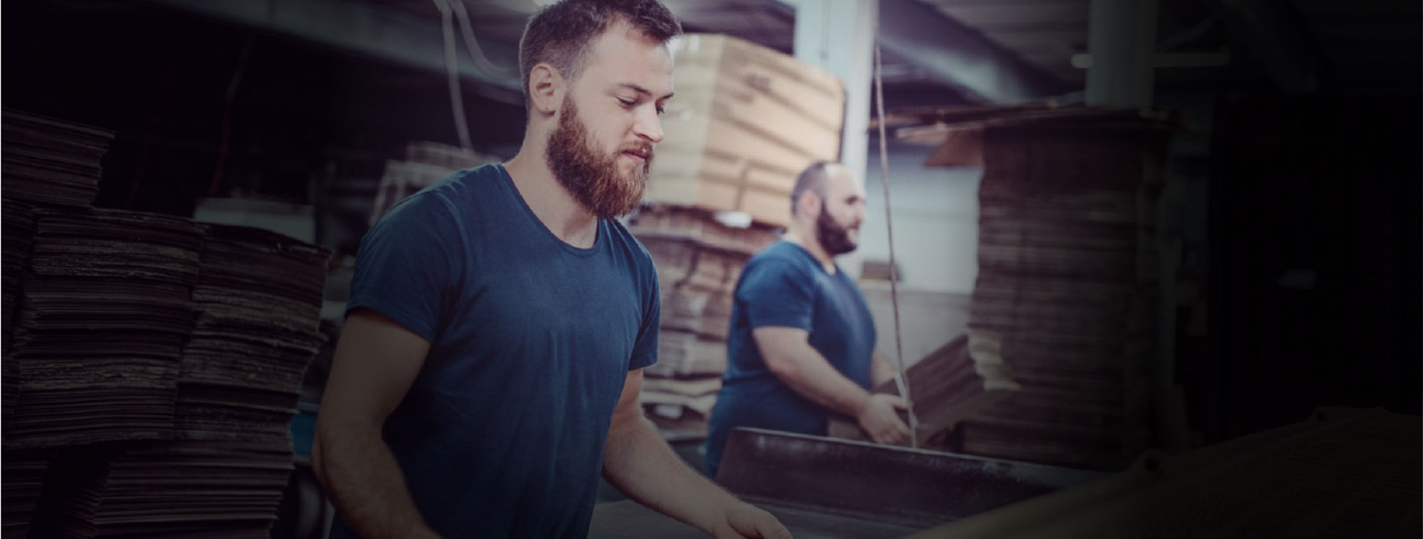 Image of two bearded frontline workers operating in a factory.