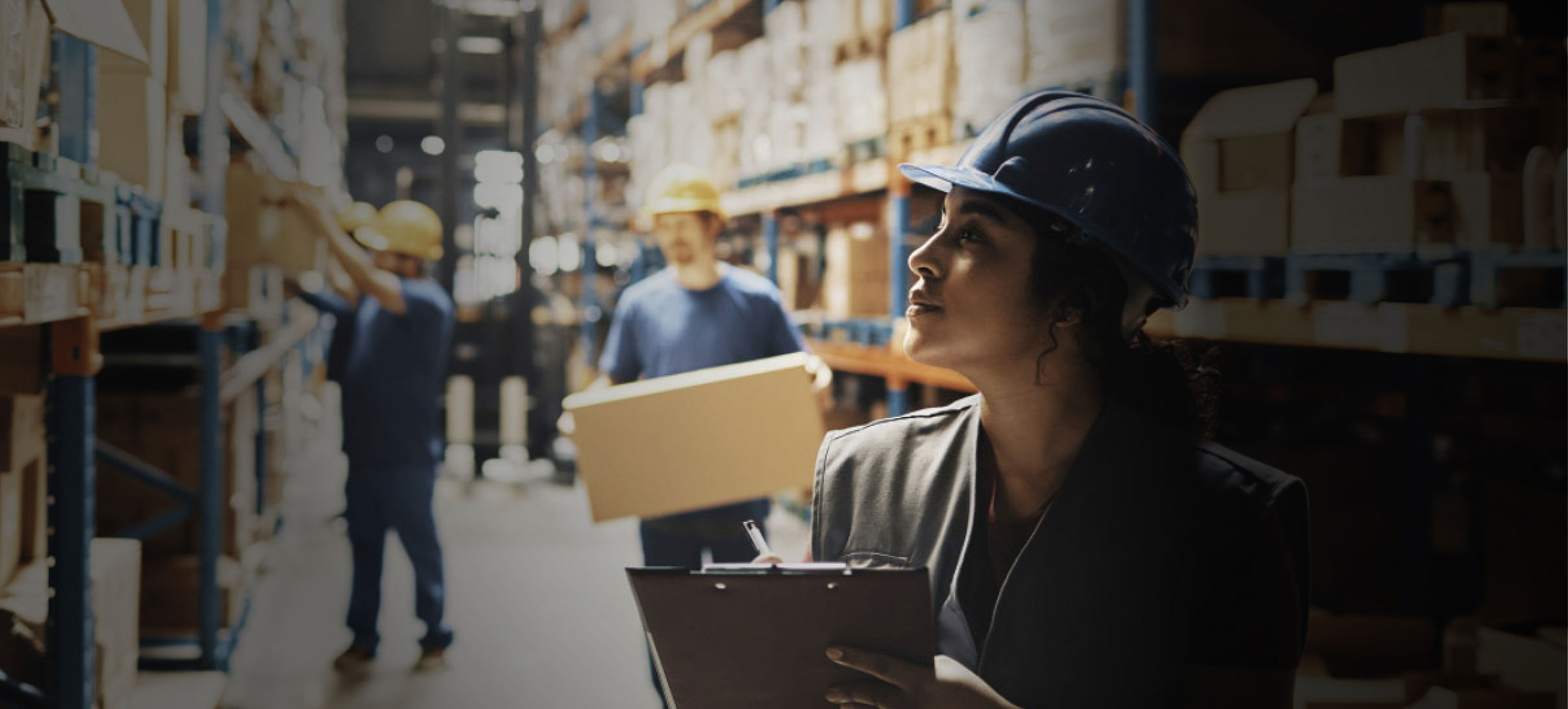 Image of a frontline worker inside of a warehouse wearing a hard hat and taking inventory, while in the background other workers move large cardboard boxes.