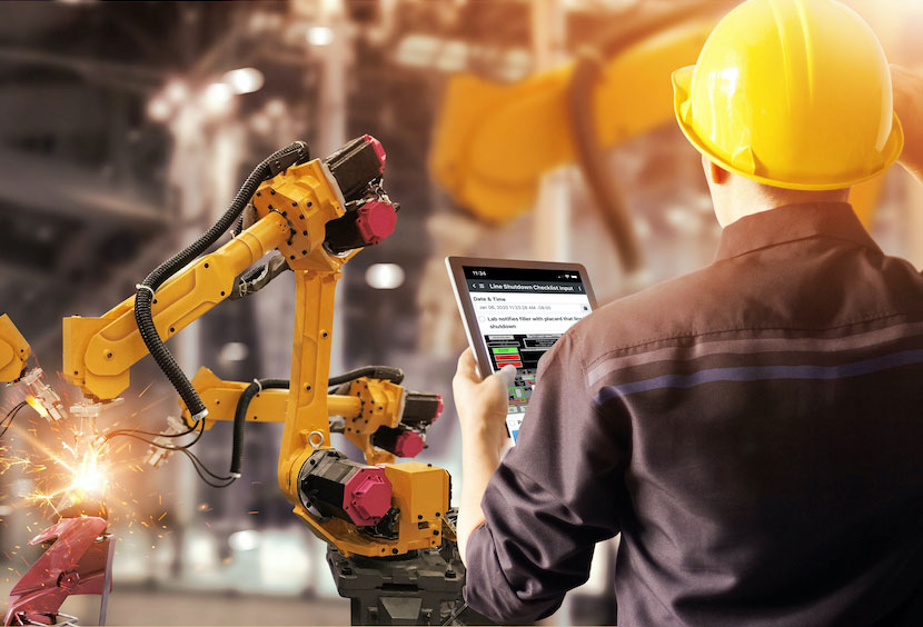 Image features  frontline worker wearing bright yellow hard hat  interfacing with the mobile Webalo app on a tablet and supervising robotic arms.