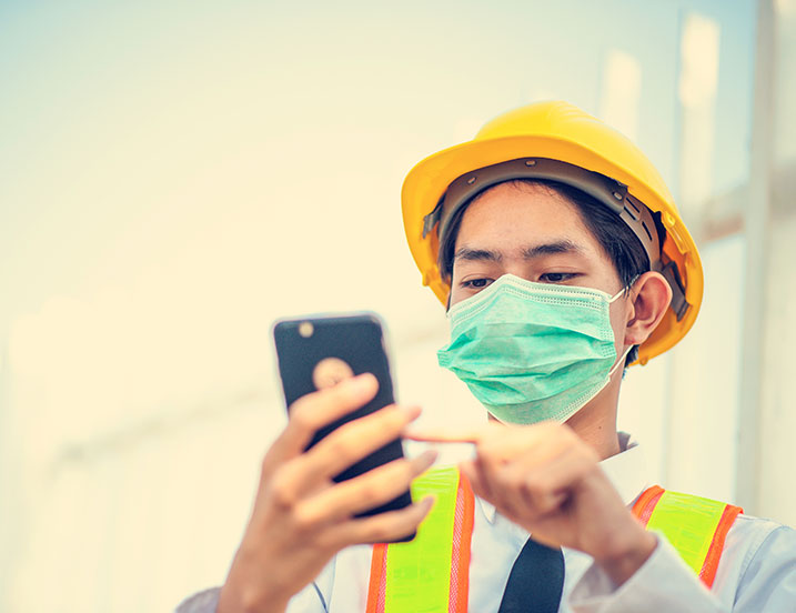 Image of frontline worker with a mask using a mobile device.
