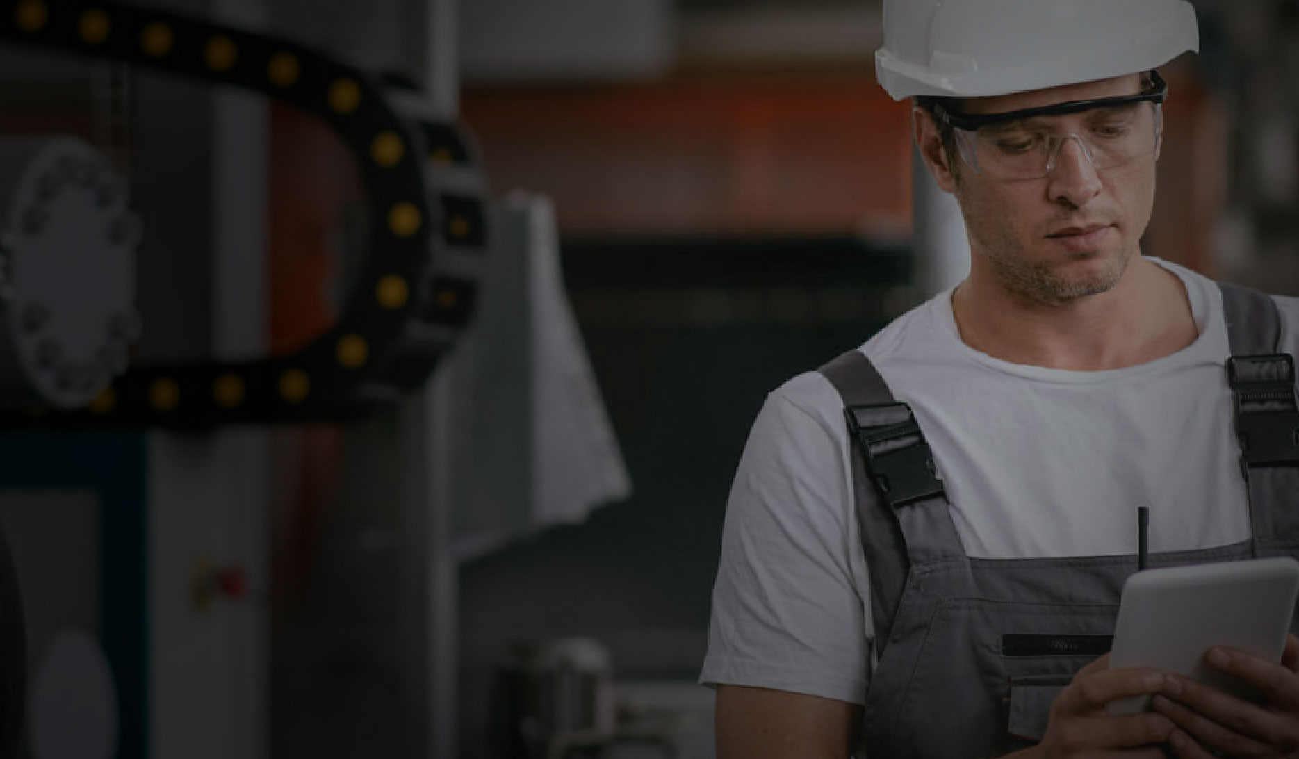 Image shows a frontline worker wearing safety glasses and a grey hard hat, using a mobile tablet within a warehouse.