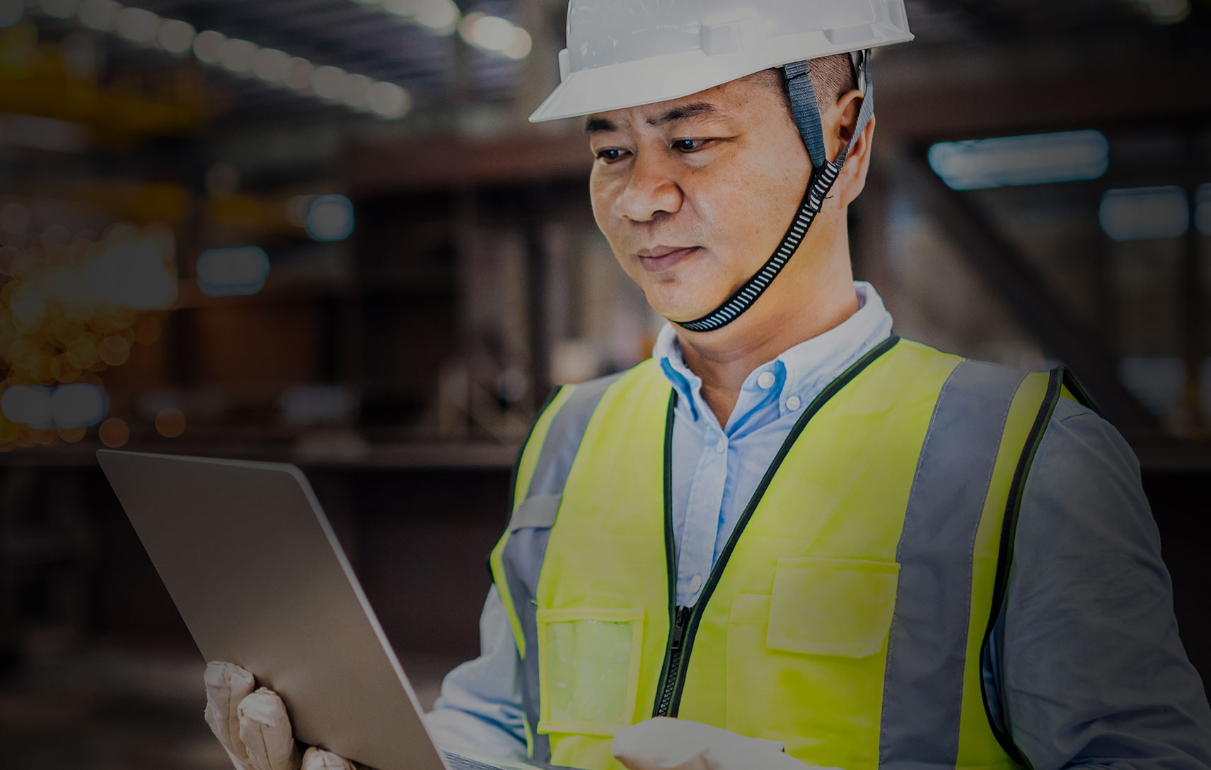 Image of a frontline worker wearing a yellow safety vest and a hard hat and using a laptop for Connected Digital Distancing.