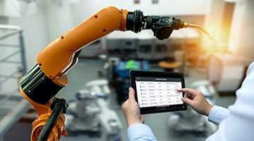 A frontline worker uses the Webalo app on a tablet in front of an automated mechanical arm in an industrial factory.