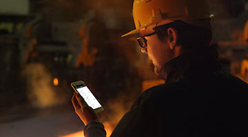 A frontline worker wearing a hard hat uses the Webalo app on a mobile phone in a plant environment.