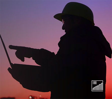Side view of frontline worker silhouetted against sunset with tablet.