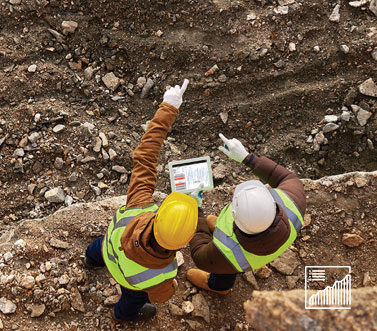 Image shows two frontline workers visualizing data on a mobile tablet in a mining environment.