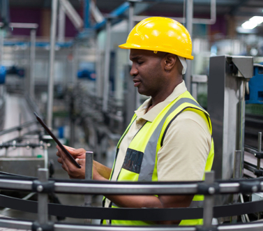 Image of a frontline worker wearing a yellow safety vest and hard hat concentrating on a mobile tablet in an industrial factory.